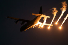 Military Plane Firing Flares During A  Night Flight.