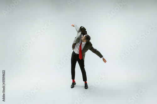 Young caucasian man moving flexible on white studio background Wallpaper Mural