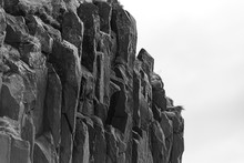 Black And White Closeup Shot Of The Big Rock Formations On The Beach