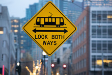 "Streetcar Caution Sign With ""Look Both Ways"", With A Cityscape Background"
