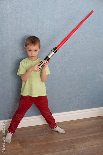 Photo boy with an evil face holds a plastic lightsaber in the room