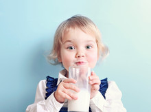 Child Girl With Glass Of Milk On Blue Background.Caucasian Kid Portrait.