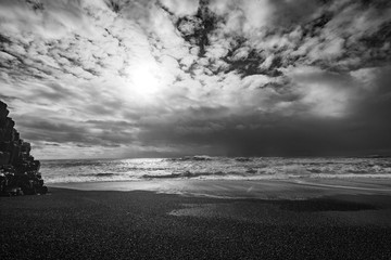 Mesmerizing peaceful view of a sandy beach and the wavy ocean in black and white