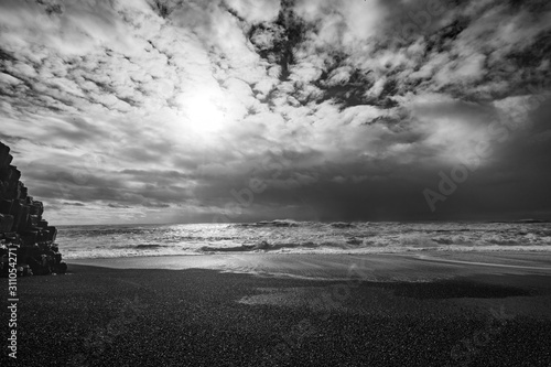 mesmerizing-peaceful-view-of-a-sandy-beach-and-the-wavy-ocean-in-black-and-white