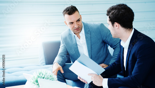 Two businessmen sitting in the office talking about marketing strategy planning, having laptops and documents for finding information Wallpaper Mural
