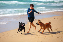 Mature Woman  Playing With Her Dogs On The Beach.