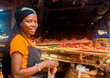 Young African Woman Selling Tomatoes In A Local African Market Smiling