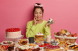 So much delicacy! Pretty thoughtful Korean woman looks with appetite at tasty creamy dessert, eats sweets cakes and pastries, poses at festive table against pink wall. Unhealthy products high in sugar