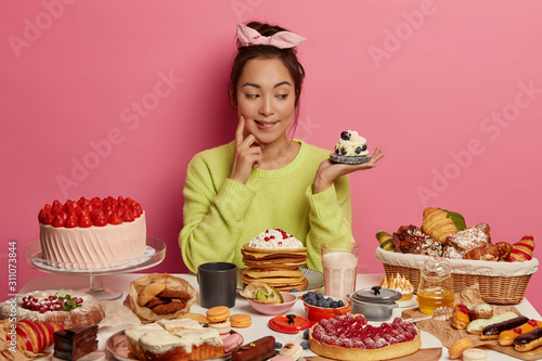 Fototapeta So much delicacy! Pretty thoughtful Korean woman looks with appetite at tasty creamy dessert, eats sweets cakes and pastries, poses at festive table against pink wall. Unhealthy products high in sugar obraz