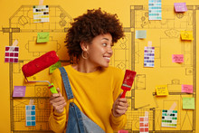 Horizontal View Of Curly Haired African American Female Decorator Holds Paint Brush And Roller, Turns Gaze Away, Thinks About Design Of Home, Busy Repairing Apartment, Wears Jumper And Denim Overalls