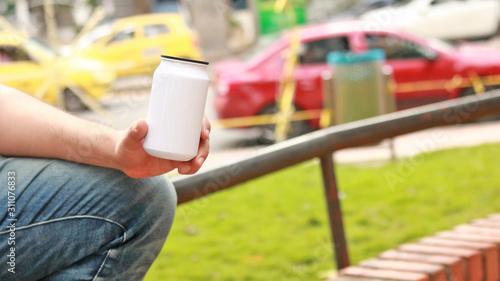 Hombre sosteniendo lata blanca con su mano, en un parque. Wallpaper Mural