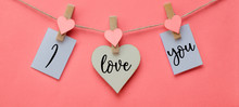 I Love You - Clothes Pegs With Wooden Hearts And Paper Notes Hang On Rope Isolated On Pink Texture Background, With Space For Text