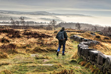 Stone Wall And Hiker Leading Into Misty Derwent Valley Landscape