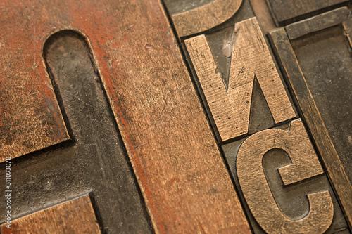 Tablou Canvas Close up of an arrangement of old wooden letterpress letter stamps