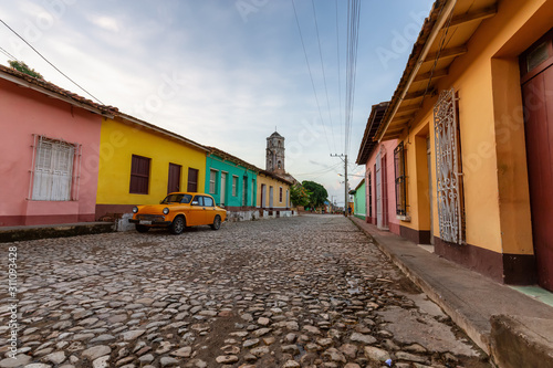 View of an Old Classic Taxi Car in the streets of a small Cuban Town with Church in the Background during a vibrant sunny sunrise Wallpaper Mural