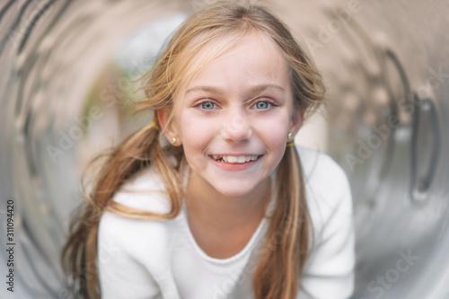 Pretty, little girl, having fun, lying on pipe on children playground Fototapet