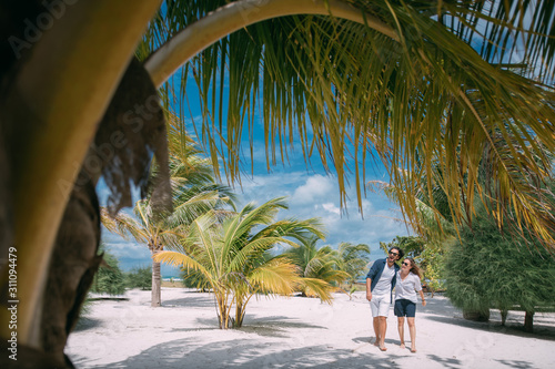 Fotografia  A pair of lovers are walking on a tropical beach.