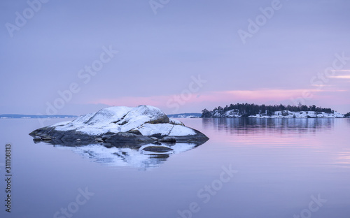 Pale purple and pink colors of a winter sunset in the Swedish archipelago outsid Wallpaper Mural