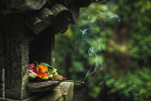 Traditional balinese Canang Sari offerings to gods and spirits with flowers, food and smoky aromatic sticks on dark green background Wallpaper Mural