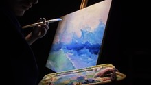 Artist Copyist Paint Seascape With Ship In Ocean. Craftsman Decorator Draw As Boat Sail On Blue Sea With Acrylic Oil Color. Draw Finger, Brush, Knife Palette. Indoor. Dark Magic Cinematic Look.