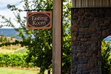 Tasting Room Wooden Classic Sign Selective Focus, Next To A Brick Wall With Vineyards In The Background, Vineyard House, Okanagan Valley, Canada