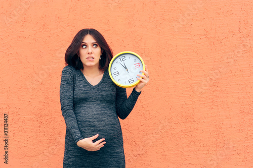 Worried Pregnant Woman Holding a Clock Awaiting her Baby Wallpaper Mural