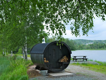 Round Wooden Outdoor Sauna With Stacks Of Wood For Heating, By A Lake With Nearby Trees And A Picnic Table.