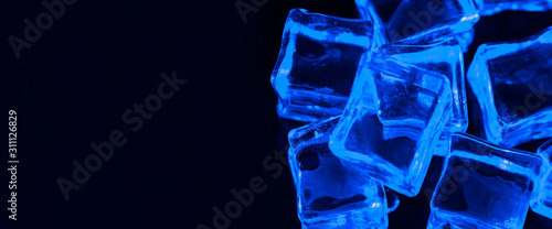 banner-ice-cubes-on-black-background-with-blue-backlight-illuminated-ice-cubes-left-empty-space-under-the-inscription