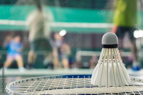 Photo shuttlecock resting on a badminton racket with badminton player are competiting