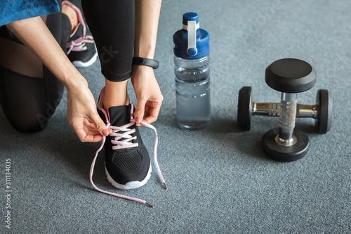 Fitness woman tying shoelaces before exercise workout at gym Poster Mural XXL