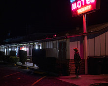 A Young Woman In A Winter Hat Under A Pink Light From A Cheap Motel Sign