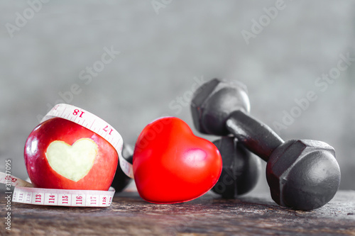 Fototapeta red apple with dumbbells ,measuring tape, sport diet and heart healthy concept  obraz