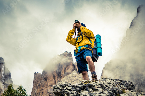 Obraz Young man hiker taking pictures on stone mountain with cloudy sky and fog. Yellow jacket, backpack, black beard and beanie. Traveling Dolomites, Italy. - fototapety do salonu
