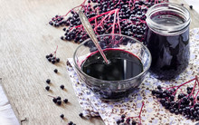 Homemade Black Elderberry Syrup In Glass Bowl And Jar