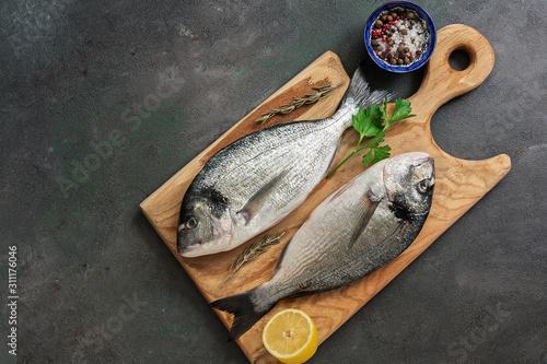 Fototapeta  Flat lay fresh raw dorado fish on a wooden cutting board, dark rustic background