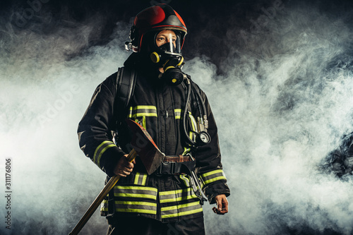 Canvas Print young caucasian fireman holding hammer, risking his life to save people from fir