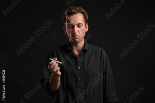 Photo Young man looking with disgust at the cigarette over black background