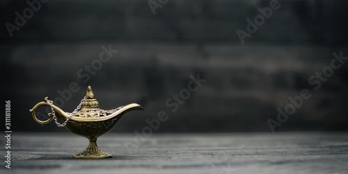 Stampa su Tela Aladdin Magic Genie Lamp on black wooden background