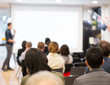 Seminar with expert speaker presenting to audience in hall. Blank business presentation screen for copy space. Executive presenter giving a speech. Leadership training coach in workshop lecture.