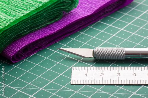 Fotografia Scalpel and ruler near colorful grunge paper.