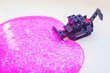 Leinwanddruck Bild - Black toy bulldozer from designer cubes removes pink gel with sparkles inside on a white background close-up top view