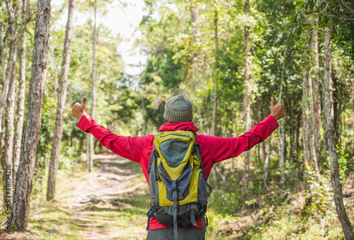 Fototapeta Hipster Hikers wear red raincoats, green backpacks, travel into the deep forest. obraz