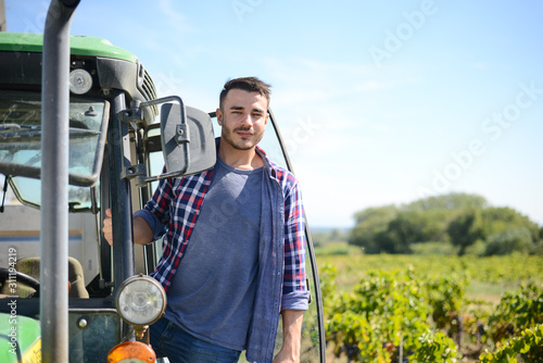 handsome man farmer in the field driving a tractor agriculture agronomy business Wallpaper Mural