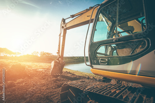 The orange backhoe is on the ground with sunset. Canvas Print