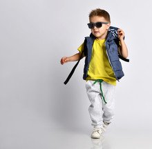 Attractive Little Boy In Stylish Warm Clothes With A Backpack On His Shoulders, Having Fun On A Light Studio Background.
