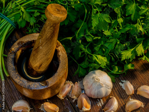 Photo Close-up of a mortar and pestle with garlic, fresh parsley and extra virgin oliv