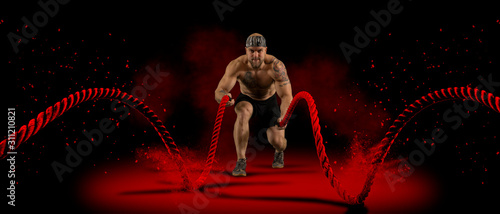 Man working out with battle ropes Obraz na płótnie