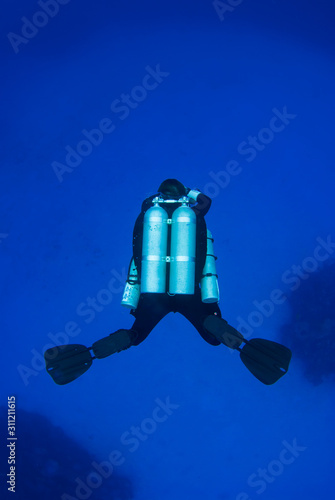 A deep technical diver has a set of doubles or twin set on his back in addition to two stage tanks on the side Wallpaper Mural