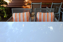 Armchairs And Pillows With White Glass Table And Reflection Of Trees