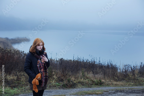 Photo Sad teenager girl with  teddy bear on country road by foggy  lake